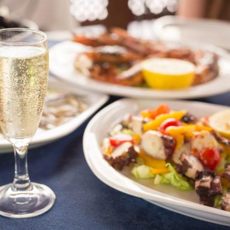 Italian cuisine. Glass of prosecco and variety of seafood. Shallow DOF horizontal